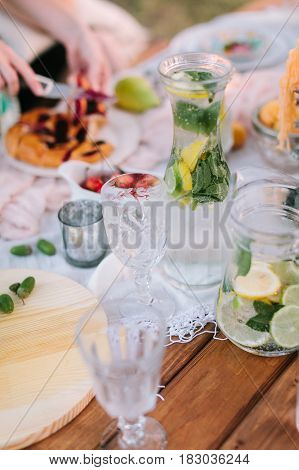 picnic, vegan food, holiday concept - delicious full pitchers of lemonade, sliced lemons, lime, mint leaves, glassware, sliced apple pie, cherries and acorns on festive wooden table with white cloth