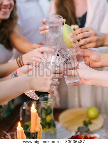picnic, people, holiday concept - happy young people clink glasses near table with flagon of lemonade and candle, one glass with whole pear instead of lemonade, flagon with lemons, limes, mint leaves