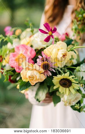 bouquet, people, flower holidays , gift and floral arrangement concept - close up of beautiful summer bouquet in hands of young woman, holding vase at nature background, art decoration work, vertical