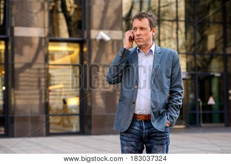 A middle age businessman standing in front of an office building while talking on his phone