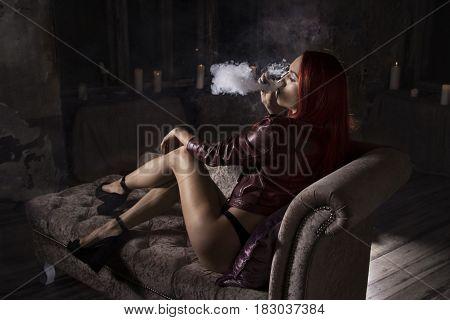 sexy woman smoking electronic cigarette and lying on the sofa, vape mod concept