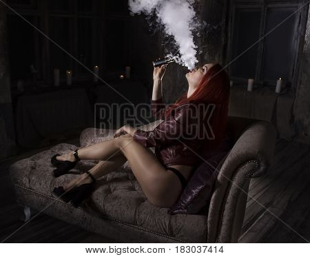 Young redhead sexy girl on the sofa vaping and releases a cloud of vapor.Studio shooting.Medieval decoration