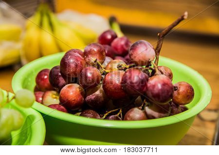Fresh red grapes on a wooden table.