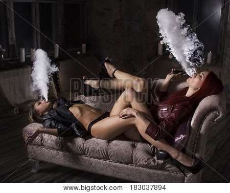 Sexy vaping vaponizers and clouding, girls with sexy bodies lying on the sofa and smoke electronic hookah