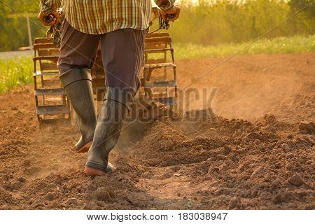 Man working in the garden with garden tiller. Garden tiller to work.