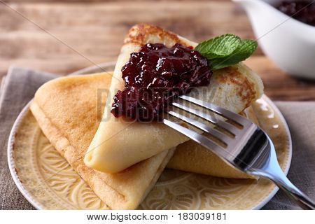 Plate with delicious pancakes and berry jam on table