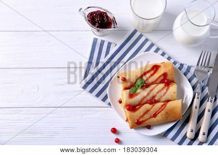Plate with delicious pancakes and cranberry on table