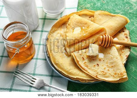 Plate with delicious pancakes and honey on table