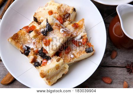Delicious bread pudding with nuts on table