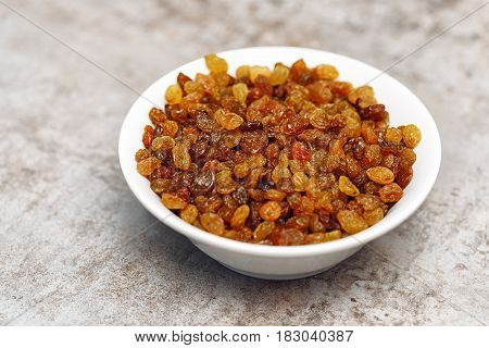 Raisins in a bowl. Dry yellow and orange grapes.
