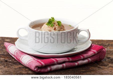 speckknoedel a tyrolean dumpling in broth on wood
