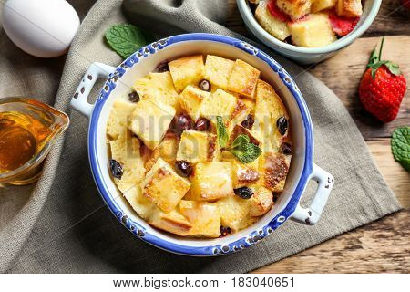 Delicious bread pudding with berries in bowl on napkin