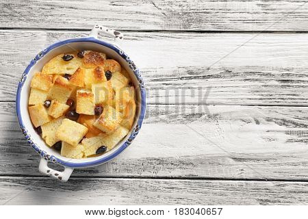 Delicious bread pudding with currant on wooden table