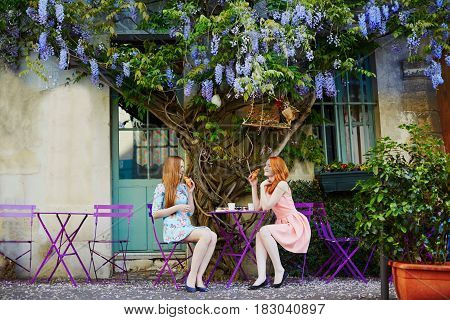 Parisian Women Drinking Coffee Together In An Outdoor Cafe With Wisteria In Full Bloom