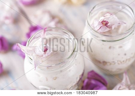 Home-made yogurt close-up with flowers. Healthy breakfast from yoghurt with muesli. dessert,