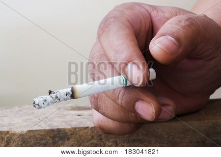 Burning cigarette with ash and smoke  on the outdoor wooden table. Bad habit concept background.