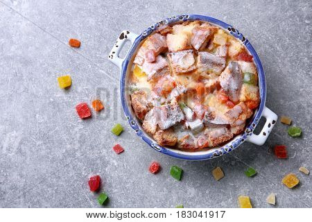 Freshly baked bread pudding in casserole dish on grey background