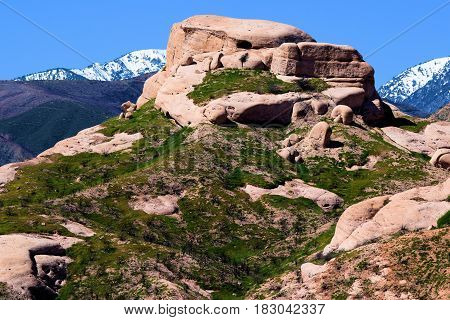 Rock formations being uplifted by the San Andreas Fault surrounded by green grasslands during spring with snow capped mountains beyond taken in Cajon, CA