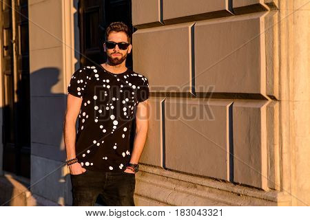 A handsome young hipster man leaning to the wall of a house on a sunny street and relaxing with his sunglasses on