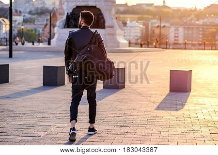A handsome young hipster man walking and looking around on a square in the sunset