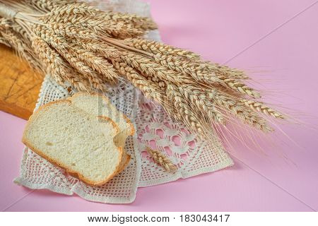 Ears of wheat and white bread rusks on a wooden board
