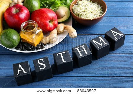 Fresh products and black cubes with space for text on wooden background. Asthma concept
