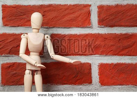 Wooden Figure On A Brick Wall Background