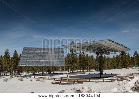 Two Large Articulating Solar Panels over snowy fields
