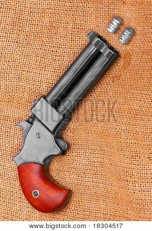 An antique 2 shot .45 cal percussion derringer hand gun. Self defense weapon.