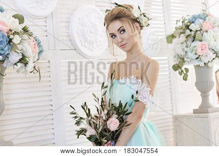 Bride in a beautiful turquoise dress in anticipation of wedding. Blonde in lace dress sea green with a bouquet . Happy bride emotion joy on his face. Beautiful makeup manicures and hairstyles women