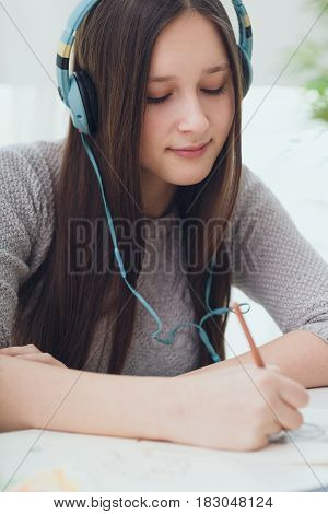 Teenage girl painter sitting in headphones while studying at home and drawing scetch by pencil