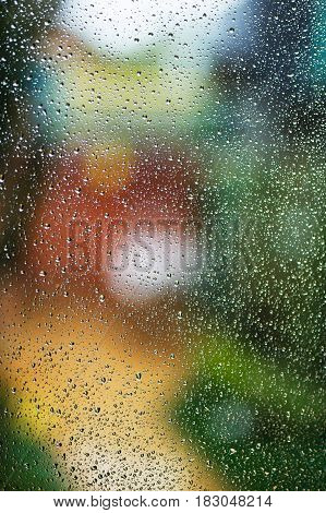 Drops of rain on window with abstract bokeh lights.