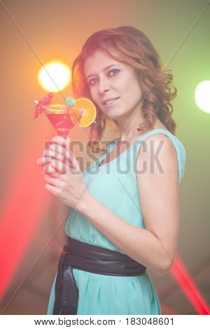 red-haired beautiful girl in a nightclub dancing under the light colored spotlights