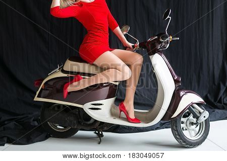 the charming sexy young woman in a short red dress and red shoes on the moped on a black background in studio. Retro shot. Fashion art photo.