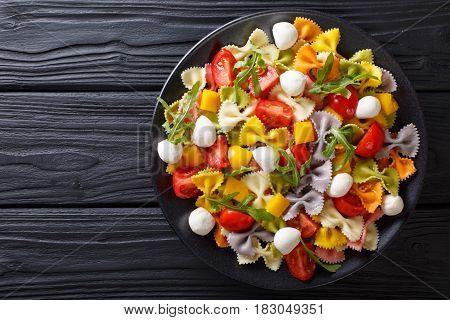 Warm Salad Of Farfalle Pasta, Tomatoes, Arugula And Mozzarella Closeup. Horizontal Top View