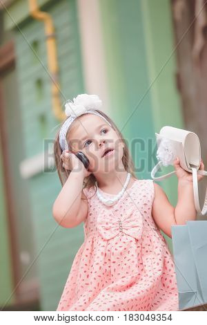Smartphone is held by child near ear. Little beautiful girl in pink dress is holding a handbag in hand and talking on mobile phone.