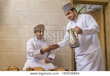 Nizwa Oman 26th May 2016: omani man serving traditional coffee called qahwa to another omani man