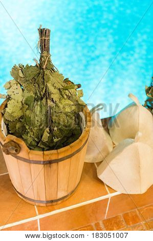 Oak Leaf Venik With Dried Herbs in wooden sauna bucket and sauna hat on a pool background. Medical sauna broom and health Venik for body. Russian banya and sauna accessories. relaxation concept.