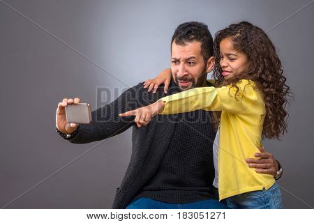 A black father taking selfies with a smartphone while his young daughter hugging him and pointing to the phone