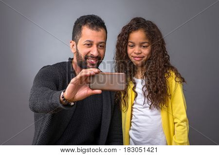 A black father and his young daughter smiling and taking selfies with a smartphone