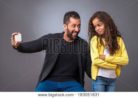 A black father taking selfie with a smartphone while his young daughter standing with her arms crossed