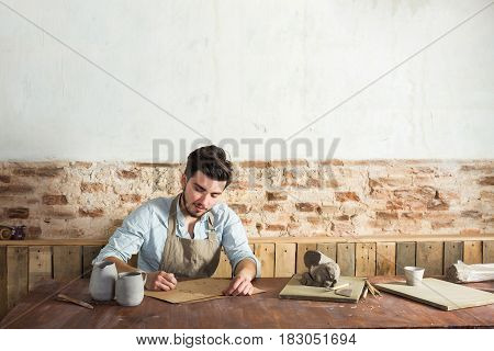the smiling handsome young mexican potter does sketches of ceramics on the paper. concept of small business, handcrafted, hobby work. horizontal picture with empty space for the text.