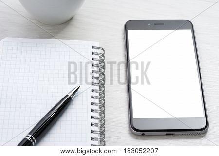 Smartphone and notepad on wooden table .