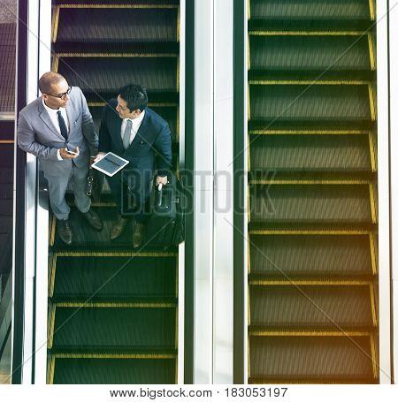 Businessmen discussion using escalator