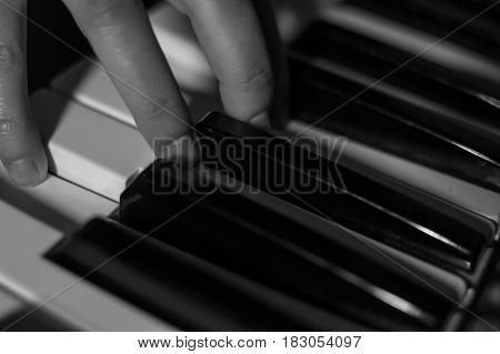 Close-up black and white atmospheric photography of a hand playing the piano. Concept: Music creating, composing, lyrics
