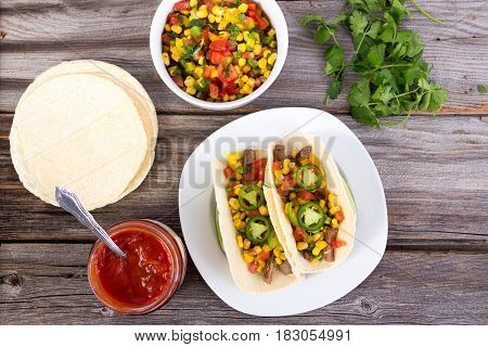 beef corn soft taco on rustic wood table with corn salsa