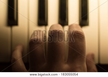 Close-up toned atmospheric photography of a hand playing the piano. Concept: Music creating, composing, lyrics