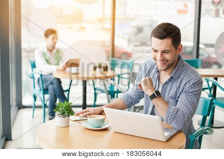 Coffee time. Handsome young man in cafe with big window. Man with cup of coffee. Man using laptop and smiling