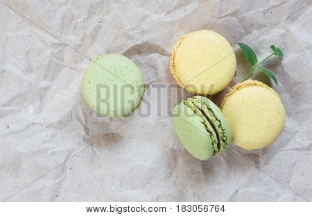 Green and yellow almond cookies (macaroons) and green mint leaves on the background of crumpled craft paper; top view flat lay composition