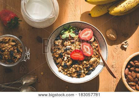 Granola, milk and fruits. Tasty and healthy breakfast: bowl of granola with fresh strawberries, jug of milk, almonds, bananas and spoons on wooden table with ray of morning sunshine. Top view